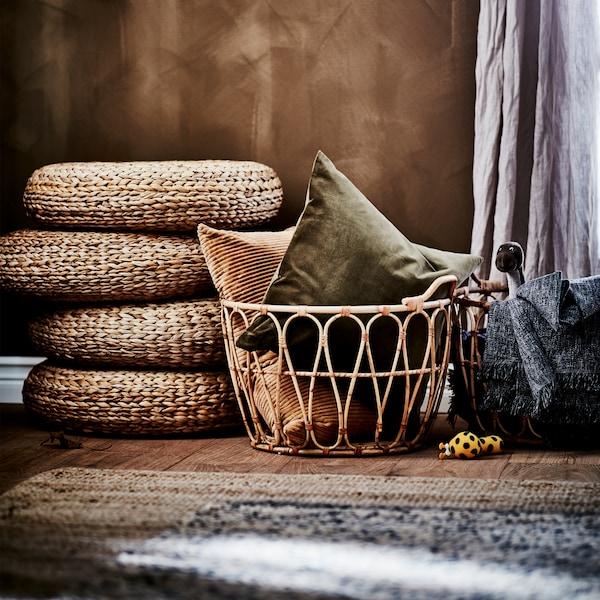 바나나 섬유로 만든 스툴 4개가 겹겹이 쌓여 있고, 2개의 라탄 바구니에 베개와 담요가 담겨 있는 모습. 주변에는 황마 러그와 리넨 커튼이 어우러져 있습니다.