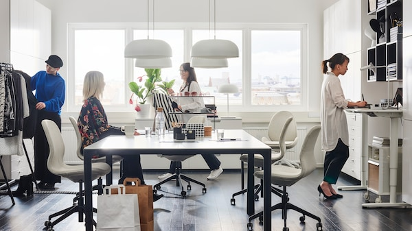4 kvinnor vid ett BEKANT arbetsbord. En sitter vid bordet de andra arbetar med olika saker.