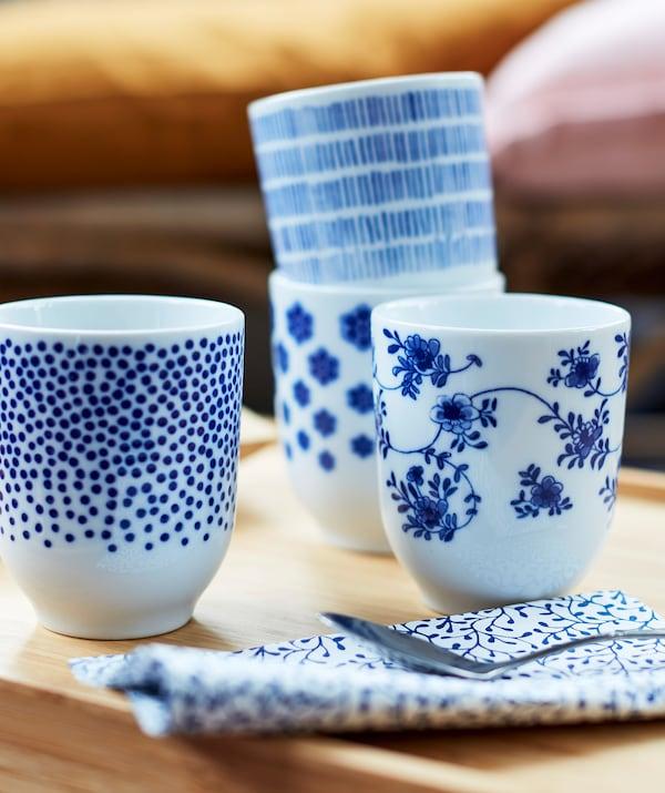 4 små, hvide tekrus dekoreret med forskellige mørkeblå mønstre.