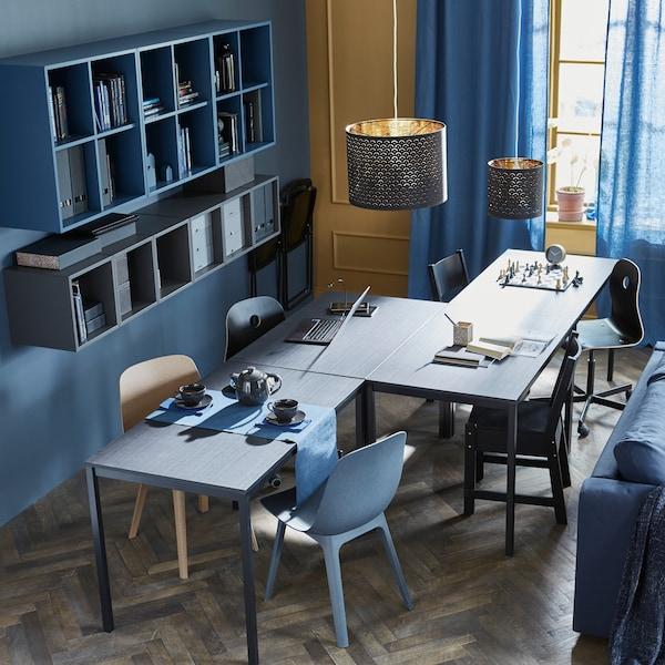 4 TÄRENDÖ Tische in Schwarz sind in einer Zickzacklinie angeordnet, damit daran verschiedene Aktivitäten, wie Schach spielen, Hausaufgaben machen und Tee trinken, gleichzeitig stattfinden können. Rundherum stehen Stühle, u. a. auch ODGER Stühle in Blau.