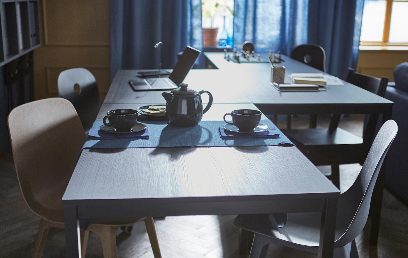 4 Tische sind in einer Zickzacklinie angeordnet & auf diesen steht ein Teeservice, ein Computer & ein Schachspiel.