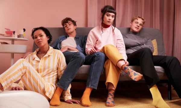4 Unifreunde entspannen sich zusammen auf einem Sofa in einem Studentenheimzimmer.
