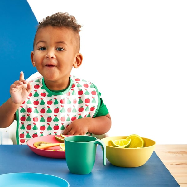 Toddler having a meal using a green cup, a yellow bowl and a pink plate.