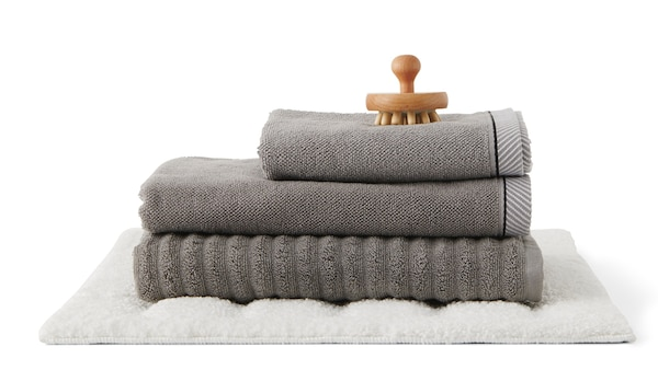 Gefaltetes graues Handtuch, Duschtuch und Badematte mit einer Holzbürste vor weißem Hintergrund.