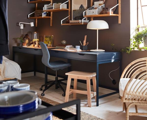 Hemmakontor med mörkblått skrivbord, väggmonterad hyllkombination i bambu, vit bordslampa och björkpall.