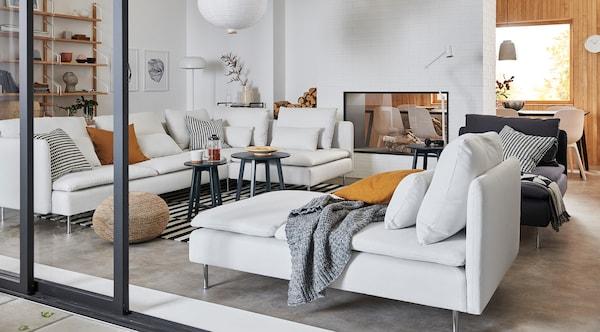 Un salon cosy et chaleureux avec des canapés blancs modulables, des tables gigognes. Des coussins et un plaid se trouvent sur les canapés. Un tapis et un pouf sont posés au sol.