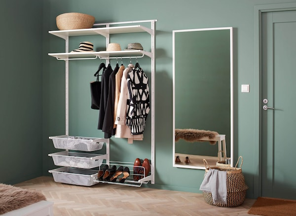 A wall-mounted shelving system with hanging clothes rails and baskets next to a white mirror against a green bedroom wall.