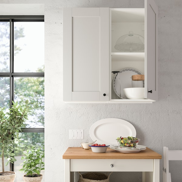 A KNOXHULT grey wall cabinet with a door is mounted on a kitchen wall, and one door is open to show storage inside.
