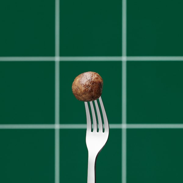 A cooked IKEA plantball on the end of an upright silver fork, against a green and white, check pattern background.