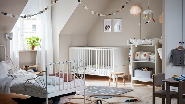 A shared children's bedroom with wood floors, a white SOLGUL cot, white changing table, and white MINNEN extendable bed.