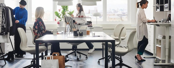 A bustling office setting with BEKANT conference table and HATTEFJALL office chairs