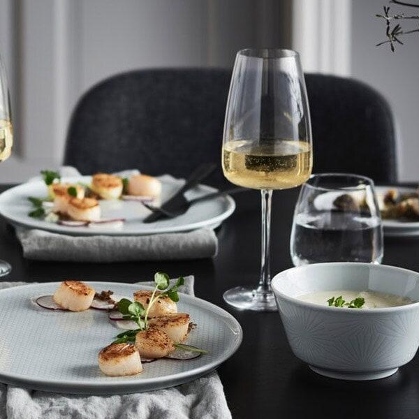 Dyrgrib vinglas med hvidvin i står op et spisbord.