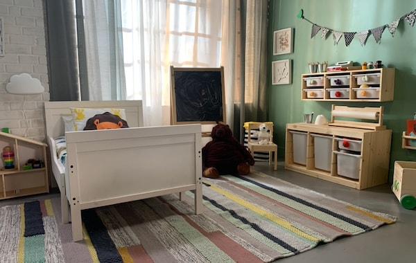 Fotografia de um quarto de criança com uma cama extensível, um cavalete e uma zona de arrumação para brinquedos.