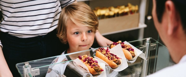 A young boy behind a glass counter looking at three veggie dogs in front of his parent.