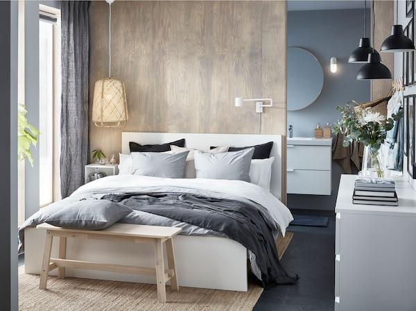 Bijeli IKEA MALM okvir kreveta s posteljinom bijele i sive boje u maloj spavaćoj sobi s drvenim detaljima.