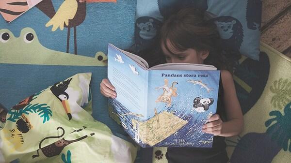 Девочка отдыхает и читает книгу о невероятных приключениях панды