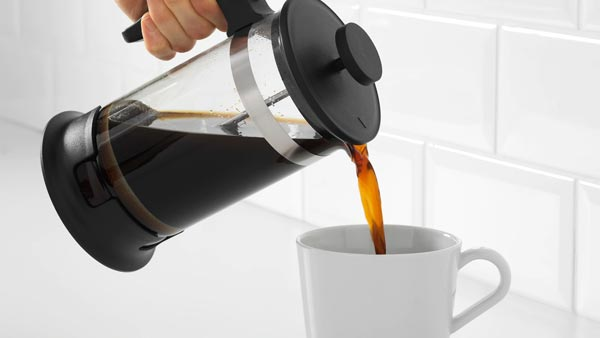 A hand pooring coffee from a UPPHETTA french press