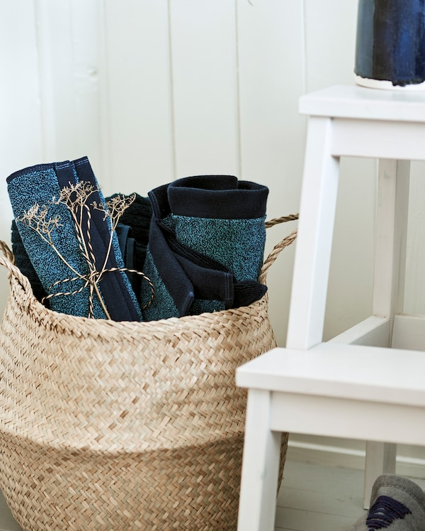 Una cesta hecha de materiales naturales entretejidos, situada junto a un taburete blanco y llena de toallas azules enrolladas.