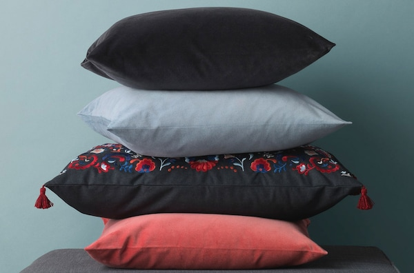 SANELA and SKOGSKORN cushions piled on top of each other.