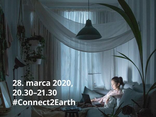Žena sediaca v prítmí domova sa zúčastňuje Hodiny Zeme.