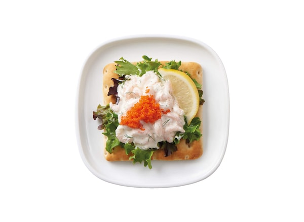 Shrimp salad on a bed of greens on a piece soft wheat bread with a lemon wedge, all on a plate against a white background.