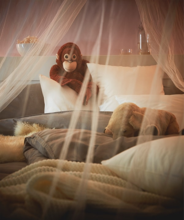 A mosquito net draped over a cozily lit, fluffy, unmade bed, a toy monkey propped up against the headboard.