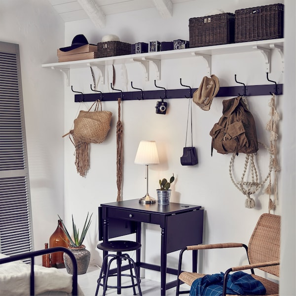 Several IKEA BERGSHULT white wall shelves and PINNIG black racks used to store jackets, bags and accessories near a small table.