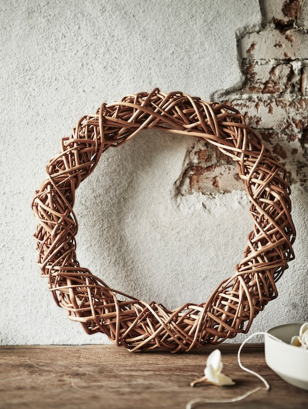 A HANTVERK wreath placed against the wall. Handmade by skilled artisans in Romania.