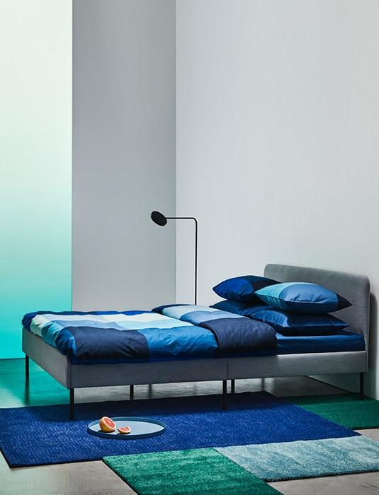 Кровать с серой обивкой и мягким изголовьем для уютной спальни