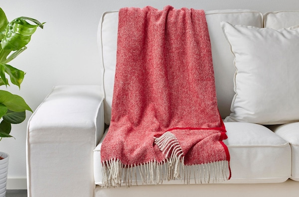 A close up of a white sofa with a red MOALIE throw draped over the back of it.