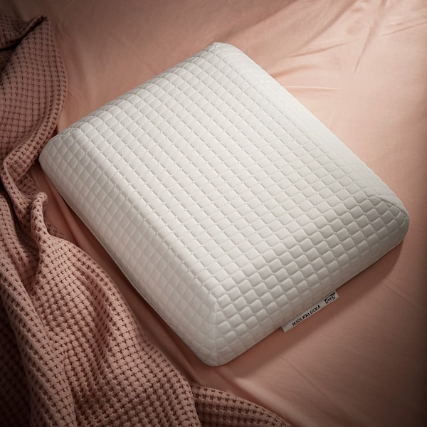The uniquely shaped IKEA MJÖLKKLOCKA ergonomic pillow, shown against powder pink bedlinen.