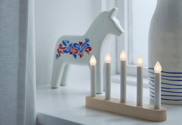 STRÅLA candelabra on a window sill with a VINTERFEST horse and white vase with blue stripes.