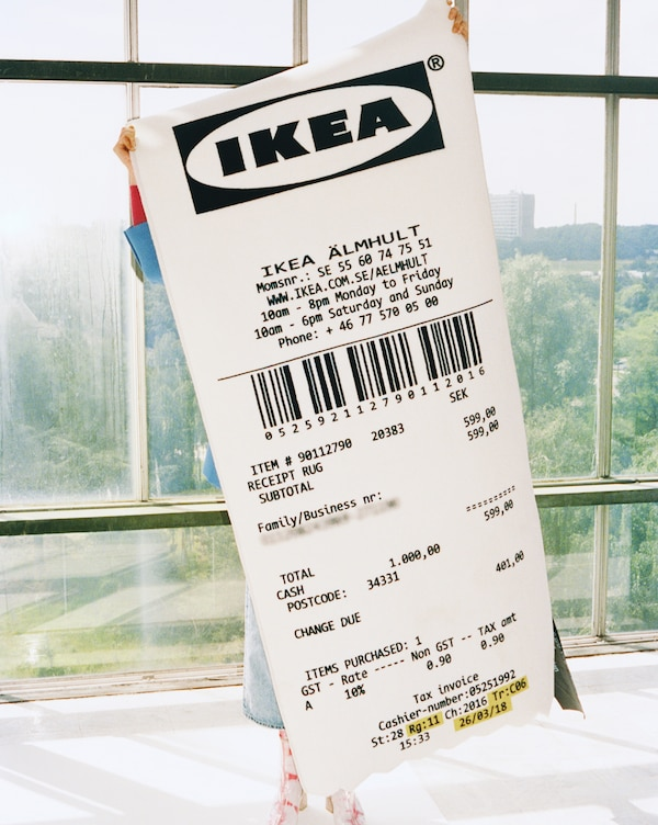 A MARKERAD rug shaped like a giant IKEA receipt being held up to the camera.