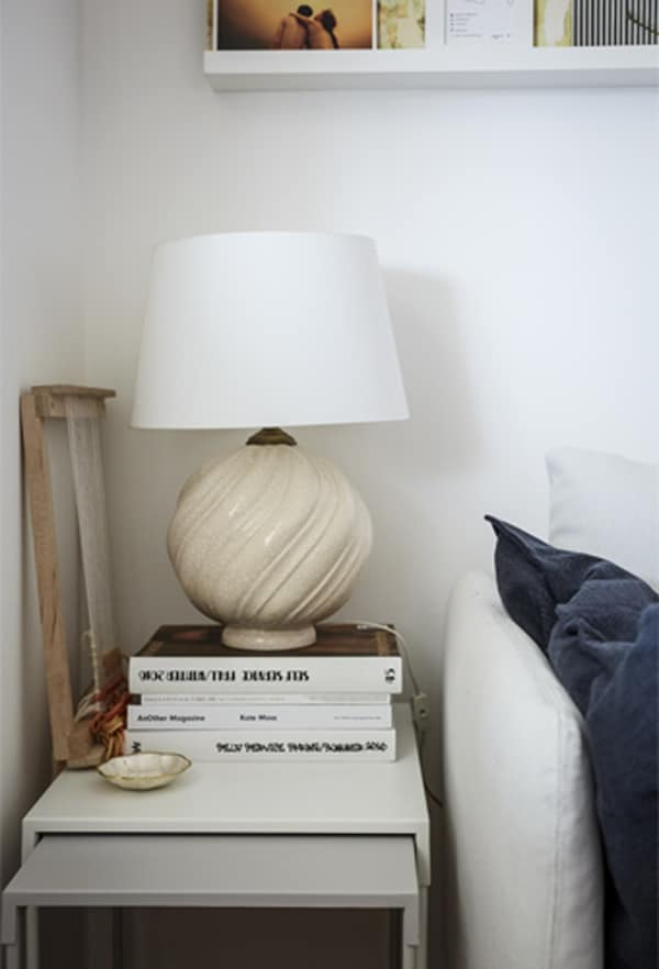 A white lamp on a pile of books on a nest of side tables.