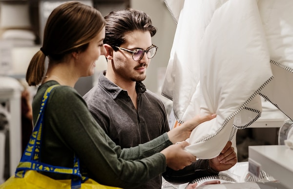 Una giovane coppia osserva e tocca un piumino in un negozio IKEA