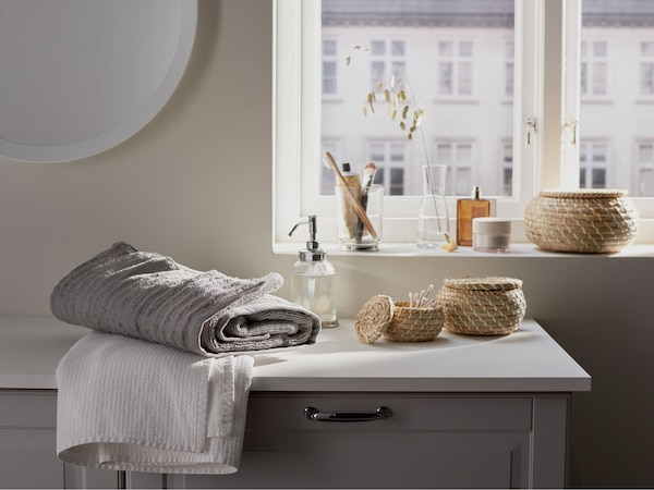 Bathroom with a GODMORGON wash stand and towels, storage and a soap dispenser on it, and a window with a view behind.