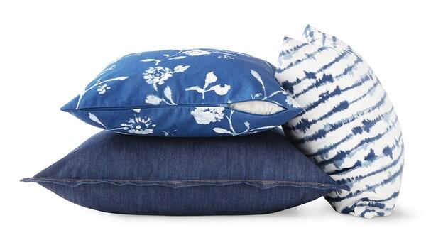Drei blaue Kissenbezüge mit blauem Print vor weißem Hintergrund