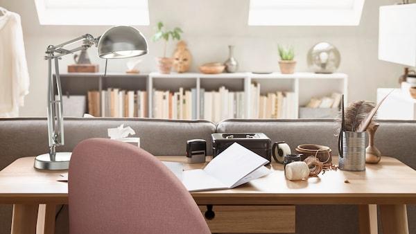 Ein Schreibtisch mit einem rosafarbenen Drehstuhl und einer metallfarbenen Arbeitsleuchte. Dahinter sind unter zwei Dachfenstern weiße Regale mit Büchern zu sehen.