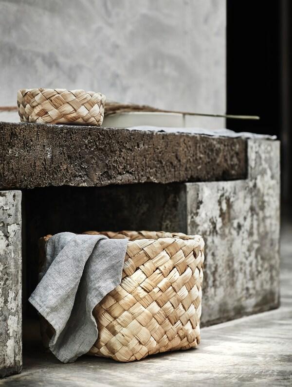 На каменной скамье стоит маленькая корзина ХАНТВЕРК. Внизу стоит корзина ХАНТВЕРК побольше. Обе корзины сделаны из банановых волокон и сплетены вручную мастерами из Индии.