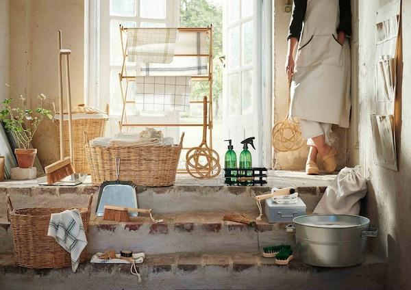 Et lyst rum med rustikke mursten og en trappe, står BORSTAD kollektionen udstillet. Kollektionen er klassisk og rustik i udtrykket med metal vaskebaljer, flettet kurve og og lyse naturlige materiale.