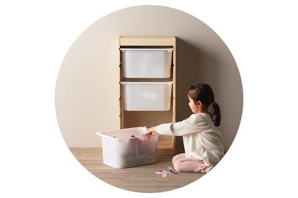 Девочка складывает игрушки в контейнер стеллажа ТРУФАСТ для детской