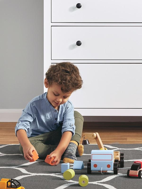 Egy kék felsőt viselő kisgyerek fa játékokkal játszik egy szürke és fehér szőnyegen, egy fehér HEMNES fiókos szekrény előtt.