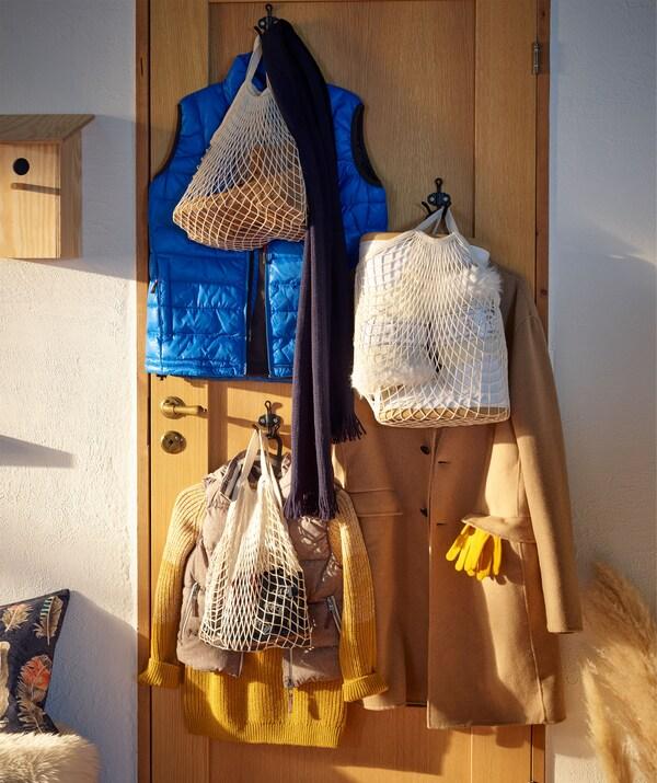 Porta de madeira com ganchos, com sinais de que os convidados já chegaram: casacos em cabides, sacos de rede cheios de objetos pessoais.