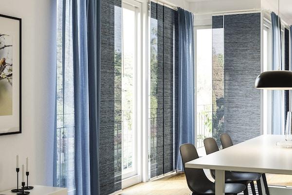 Blaue Schiebegardinen und blaue Vorhänge vor einem Großen Eckfenster mit ienem Esstisch in weiß und schwarzen Esszimmerstühlen.