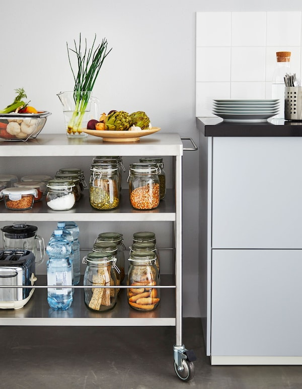 A metal kitchen island on wheels stocked with jarred ingredients sits next to a kitchen counter.
