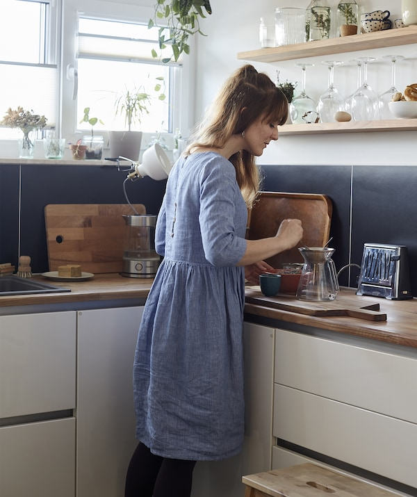 A woman making tea in the corner of a blue and white kitchen.