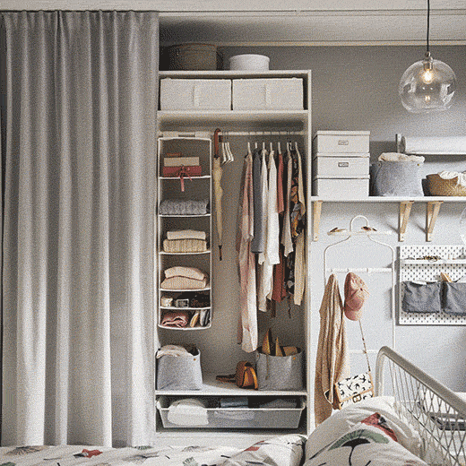 A curtain in front of a wardrobe with shelves and hanging storage.