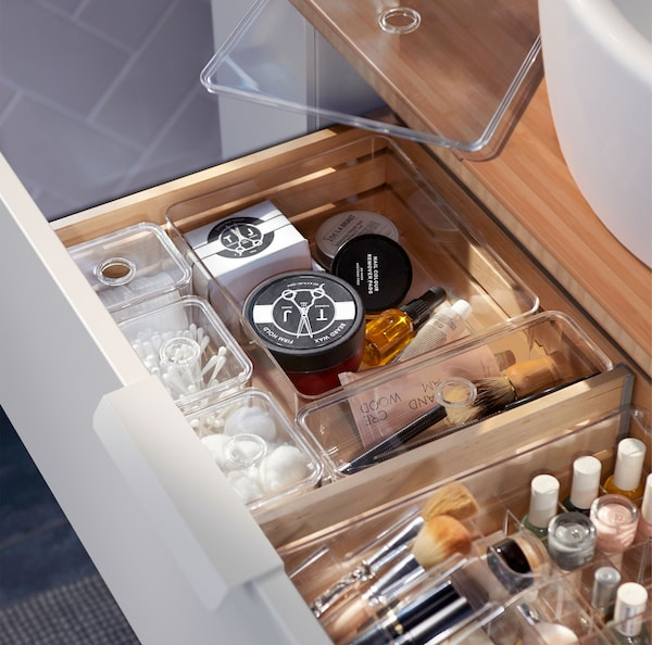 A combination of clear GODMORGON storage boxes filled with bathroom essentials placed in a wooden drawer.