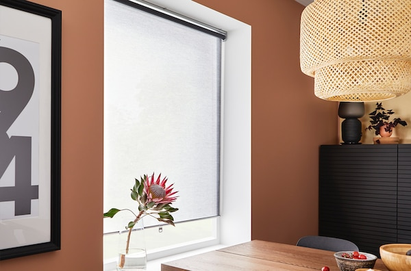 A close up of a dining room wall with a recessed window and blind.
