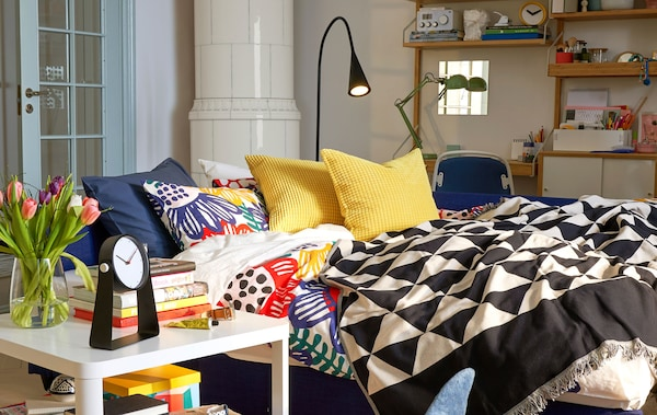 A sofabed made up as a bed in a living and work space with a white floor lamp and side table.